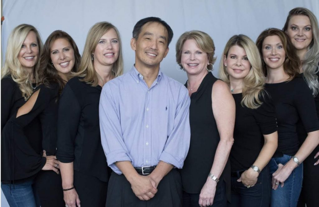 dr. chang is surrounded by the seven young ladies who work in his office