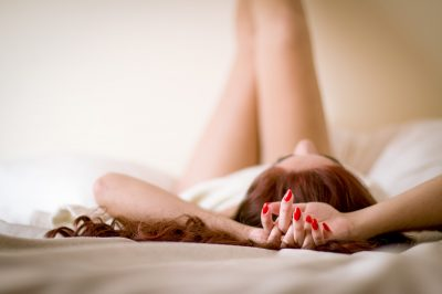 a young girl with red nails lays on a bed with her legs up in the air