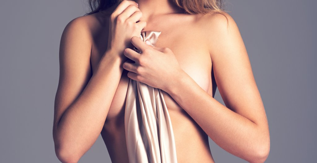 Beautiful naked girl covers the naked breast