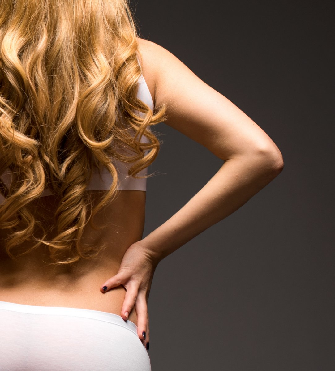 Blonde woman wearing white sporty lingerie, back view, isolated on gray background