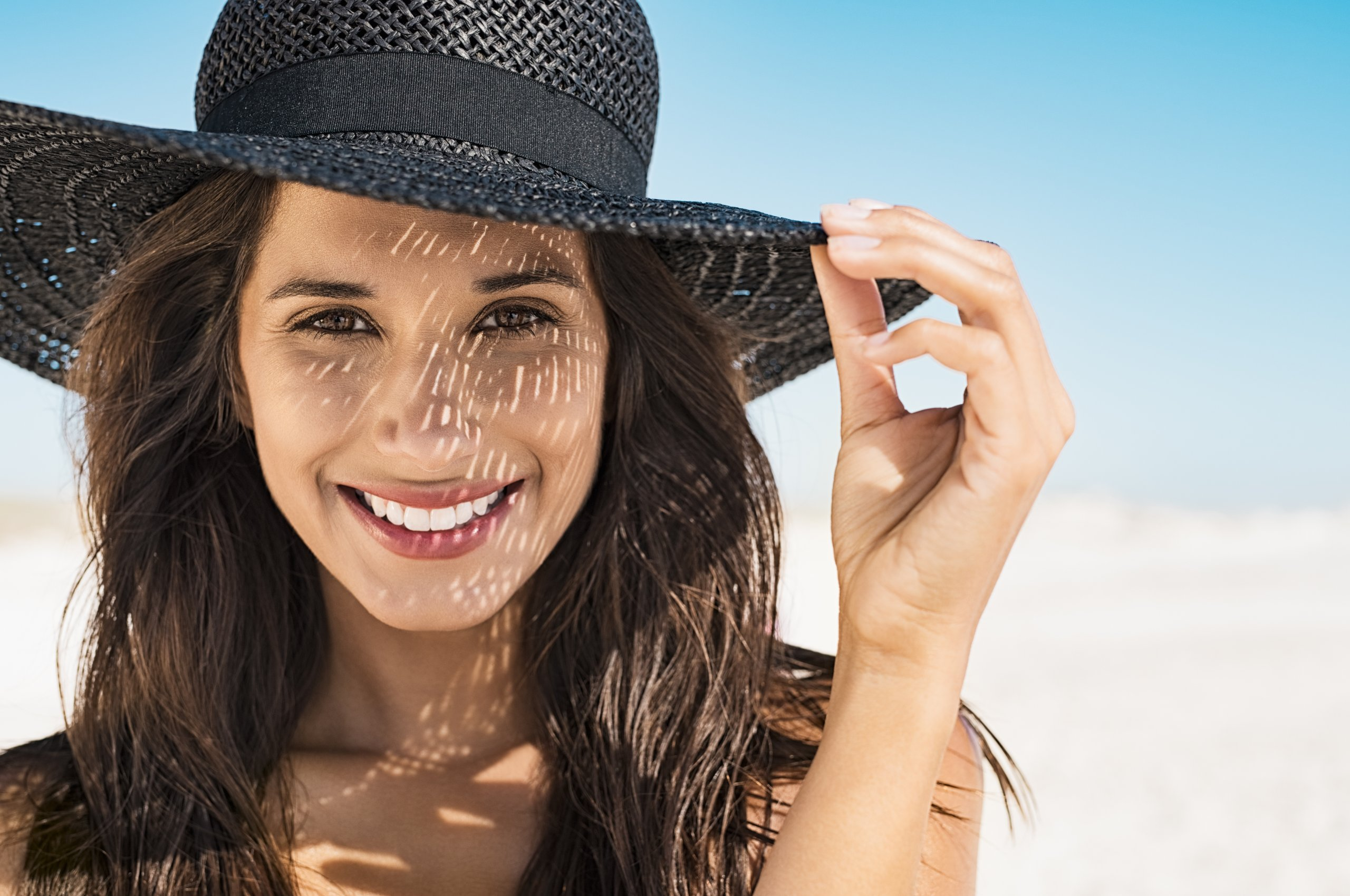 Portrait of beautiful young woman wearing summer black hat with large brim at beach. Closeup face of attractive girl with black straw hat. Happy latin woman smiling and looking at camera with sea in background.