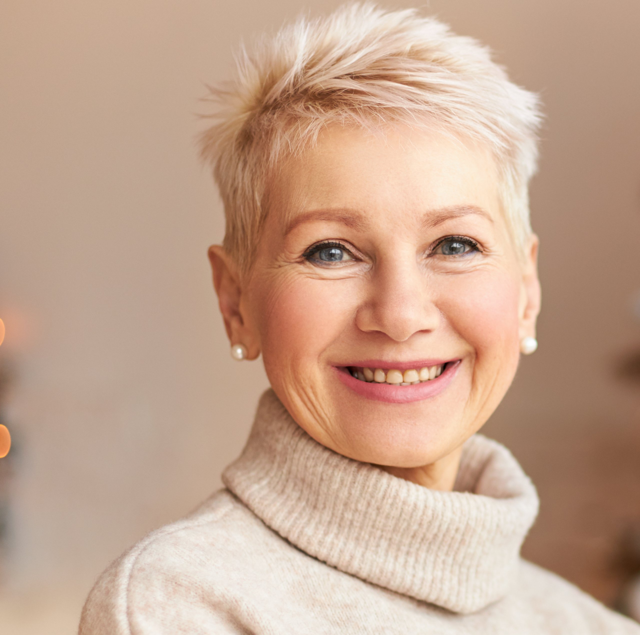 Season, winter, holiday and celebration concept. Picture of cheerful middle aged lady with short haired and broad radiant smile enjoying preparations for Xmas, posing at decorated pine tree at home