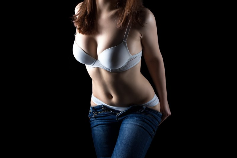 Undressing pudgy girl in white lingerie, no face on black background