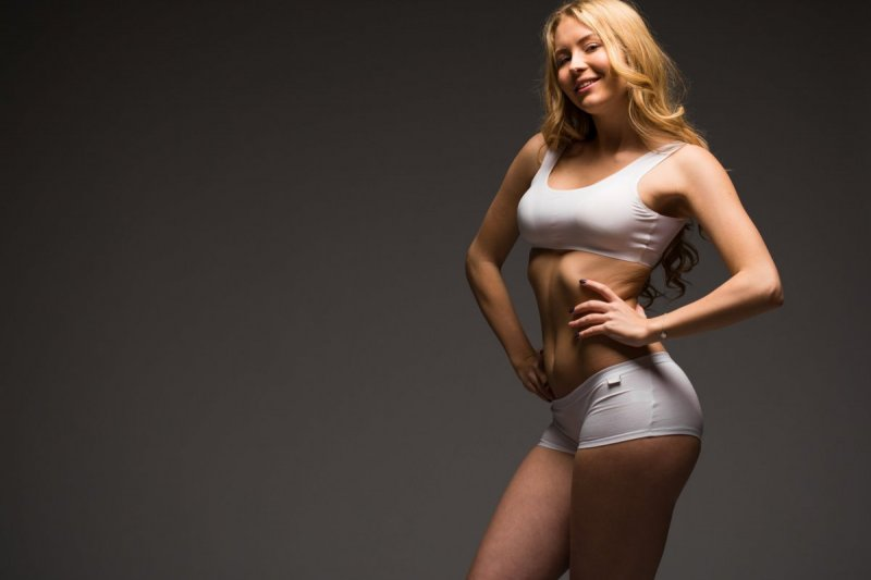 Young beautiful blonde woman in white fitness clothing, dark gray isolated background