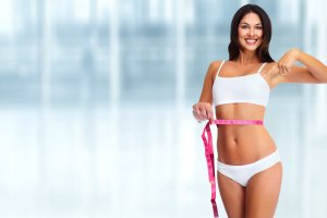 Young woman with measuring tape. Weight loss and dieting.